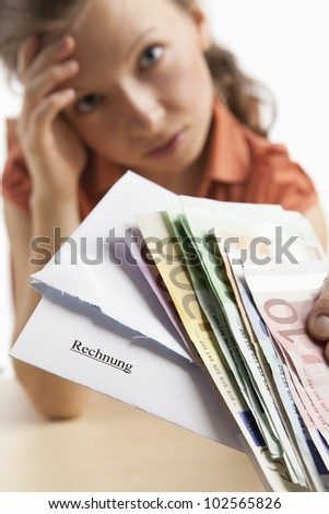 Desperate woman holds invoice and money in her hand - stock photo