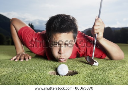 Desperate young male golf player in red shirt and putter lying on golf green and blowing golf ball into cup, focus on ball. ストックフォト ©