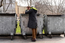 desperate young man holding his head while looking for food in dumpsters. a lonely man who has lost his job looking for food in a dumpster. the problem of homeless  people. Lifestyle of a tramp
