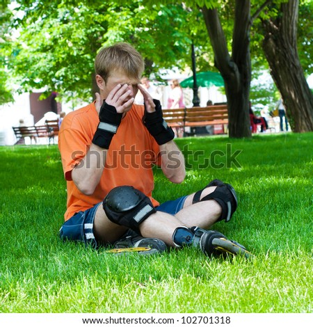 Desperate young sportsman  with headache sitting  in city park