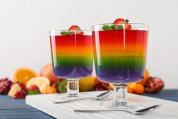 Dessert bowls of layered jelly served on blue wooden table against light background