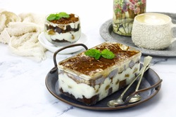 dessert box or dessert in a transparent box. consisting of pieces of cake and wipingcream. served on the table with a cup of coffee, landscape view and bright background foodphotography