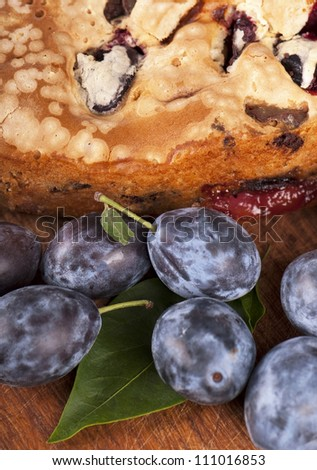dessert cakes  and fresh plums on old wooden table