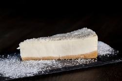 dessert cheesecake covered with dried coconut pulp, cheesecake on an individual tray sprinkled with powdered sugar