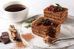 Dessert. Chocolate biscuit cake with cream, cinnamon and berries. Sweet pie with cocoa and chocolate on a white wooden board. Cup of coffee and rosemary on a light background. Copy space