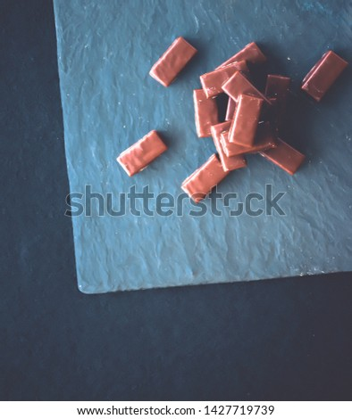 Dessert, confectionery and gluten-free organic food concept - Sweet swiss chocolate candies on a stone tabletop, flatlay