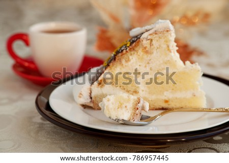 Dessert in a small spoon. A piece of cake in a dessert spoon. Cake on a silk tablecloth. Dessert in the form of a cake with the name of a turtle. A cake, a cup of tea and glare.
