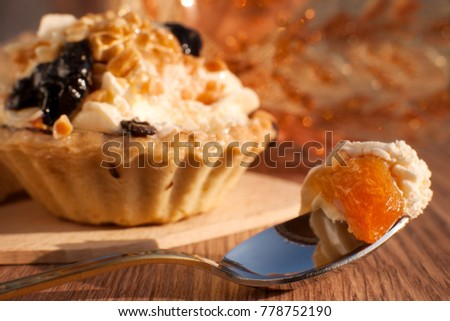 Dessert is eaten with a spoon. Macro. A piece of cake with apricot. Cake in a dessert spoon. Sweet dessert with cream on a golden background. A cake in the form of a basket.