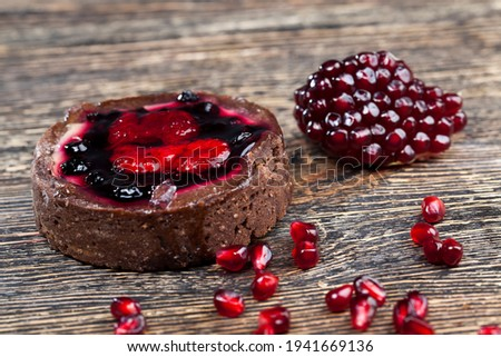dessert of baked tartlets, chocolate tartlet with fruit and berry filling, round tartlet with strawberries and blueberries in butter cream, closeup