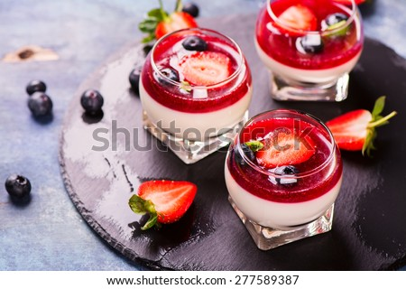 Dessert panna cotta with fresh berries on wooden background, selective focus