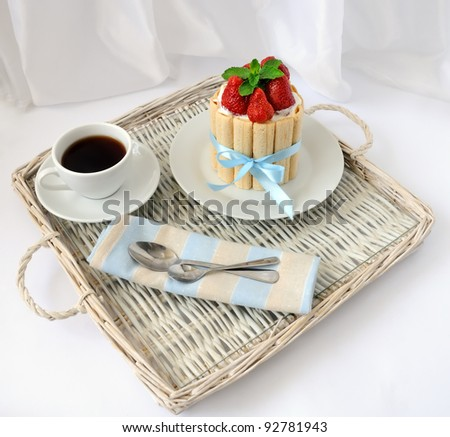 Dessert souffle with biscuit and fresh strawberries on a tray with a cup of coffee
