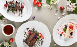 Dessert Table - created with Chocolate Cake, Classic Cheesecake and Chocolate Cheesecake. Spring flowers on vintage table with berries and tea cup. Cake slice topped with berries and chocolate s