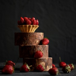 Dessert tartlet with strawberries stands on a hill on a black background. Sweetness for a loved one. Sweet passion. Red passion. Passionate impulse. Dessert for Valentines Day. Cake for March 8