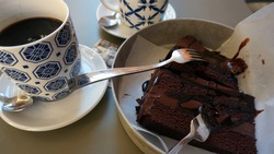 Dessert time. A large piece of chocolate cake and a cup of coffee.
