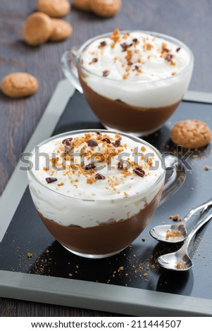 dessert with chocolate, cream and amaretti in cups, top view, vertical