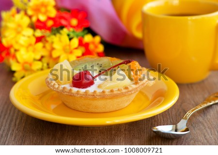 Dessert with fruits and cream. Dessert with cherries, kiwi and pineapple in a basket. Dessert and yellow cup of tea. Cake in yellow tones. Dessert on a background of flowers.