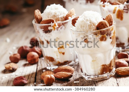Dessert with vanilla ice cream, nut sauce, almonds, hazelnuts and coconut, served in glasses, selective focus