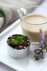 Desserts, a cup of coffee and cheesecake with chocolate on a white plate on the table. Purple flower. Background image, copy space