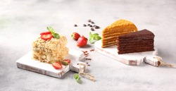 Desserts. Cakes: Napoleon, honey cake and chocolate cake on light wooden boards on a light gray table. Fresh berries, strawberries and mint, spoon. Background image, copy space, horizontal
