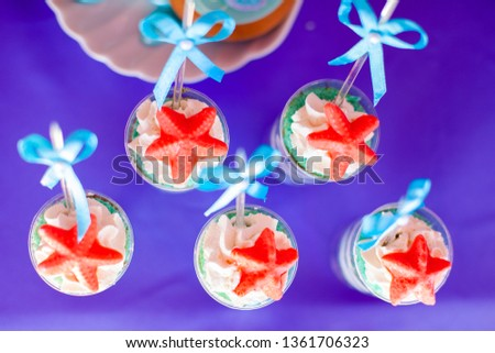 Desserts with whipped cream and sea star d cor. Candy bar for party, birthday, wedding. Purple background for prints, cards, banners.