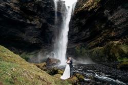 Destination Iceland wedding, near Kvernufoss waterfall. Wedding couple is standing near the waterfall. The groom hugs the bride.