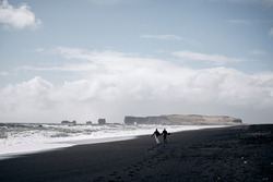Destination Iceland wedding. The wedding couple runs along the sandy black beach of Vik, near the basalt rock, in the form of pillars. Holding hands, running along the shore against backdrop of waves