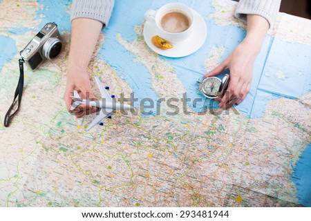Destination points. A woman sitting at table with a map, airplane, compass and camera and visualises his desire to travel.  Top view. Globetrotter coffee break for trip dreams.