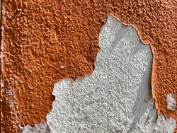 Destroyed Plastered Brick Wal, Grunge orange metal wall with peeling paint, close-up background photo texture
