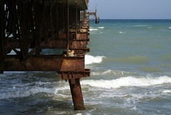 Destroyed quay in the sea. Rusty metal construction. Old pier in the waves.