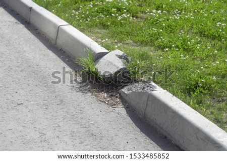 Destroyed sidewalk curb, gray concrete and lawn with bright green foliage. Sunny summer in the city #1533485852