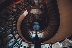 Destroyed spiral staircase indoors. Natural light. Beautiful architecture. Old apartment building in Saint Petersburg. Winding stair. Devastated ruins