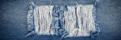Destroyed torn denim blue jeans texture. Ripped denim blue cloth background. Recycling old jeans denim concept, banner