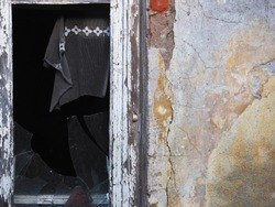 Destruction and desolation, a fragment of an abandoned house, a broken window, torn curtains