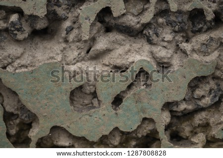 destruction by time. bulk texture of a crumbling concrete wall. erosion destroyed most of the surface and in the grooves can be seen the composition of concrete - sand, rubble, cement.