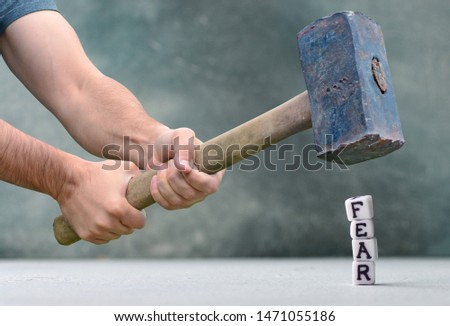 Destruction of fears concept with letters and big hammer.  #1471055186