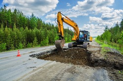 Destruction of the road surface on an intercity highway using an excavator to replace it
