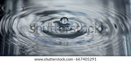 Detached water droplet rebounding from splash causing ripples #667405291