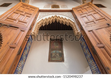 Detail angled shot of a traditional Moroccan riad, with arched entrance with big wooden doors, stucco craved details and colorful mosaic/tiles with white wall and old window frame in the middle.