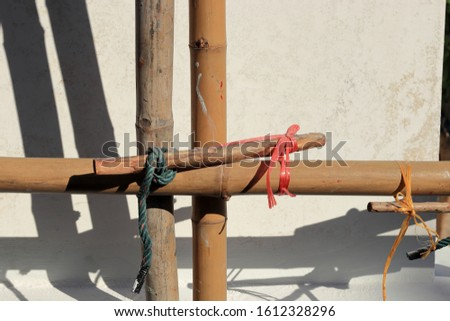 Detail close-up of scaffolding for reconstruction, made from bamboo and plastic, nylon rope.