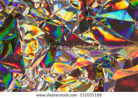 Detail close up of strongly wrinkled metallic paper as a colorful fantasy background image in rainbow colors with focus at the center