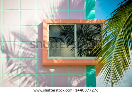 Photo of  Detail close-up of typical colorful Art Deco architecture with tropical palm tree shadows in South Beach, Miami, Florida