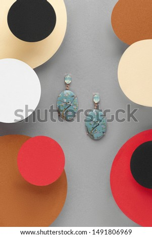 Detail close-up shot of a pair of stud earrings with smoky blue facetted gems on the fastenings and oval pendants with a drawing. Each pendant is fixed in the golden metallic setting,  #1491806969