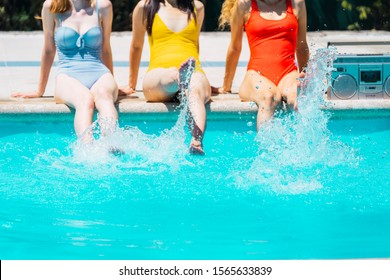 Stock photo of detail of the feet of three girls with bathing suits of different colors splashing the water of a swimming pool