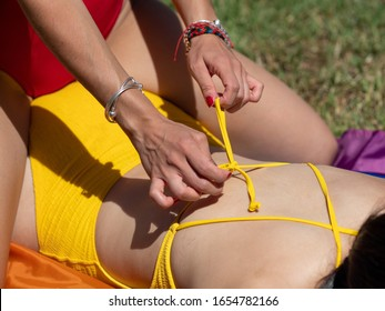 Stock photo of detail of a girl's hands unbuttoning a knot in another girl's bathing suit lying on the grass to massage her