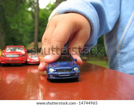 Detail hand with toy-car. Little baby play outdoor with toy