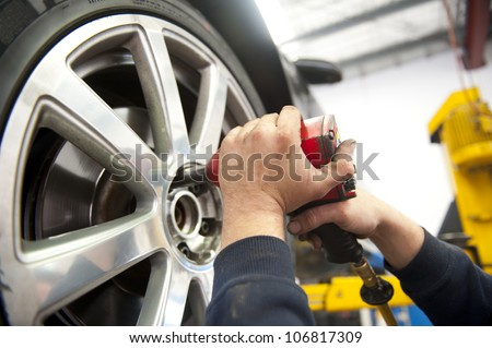Detail image of mechanic hands with tool, changing tyre of car, with blurred background of garage.