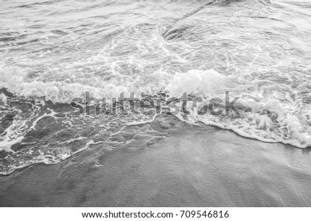 Detail in black and white of the sea waves crashing on the beach. The water in contact with the yellow sand forms the white foam. Zdjęcia stock ©