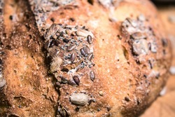 Detail in selective focus on the crust of a homemade wholemeal bread with a mix of seeds on the surface (flax, sunflower, poppy and anise)