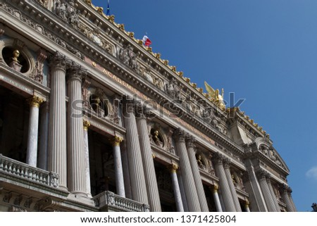 Detail looking up at the Palais Garnier - Academie Nationale De Muisque - home of Opera in Paris, France. Columns (pillars), gold detailing, statues and carvings above doorway / entrance #1371425804