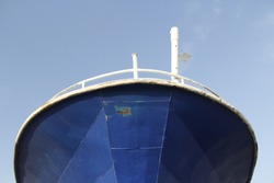 detail looking upward of steel fishing vessel royal blue paint and cloudless sky